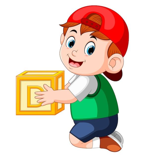 Маленький мальчик, держащий кубик алфавита Premium векторы