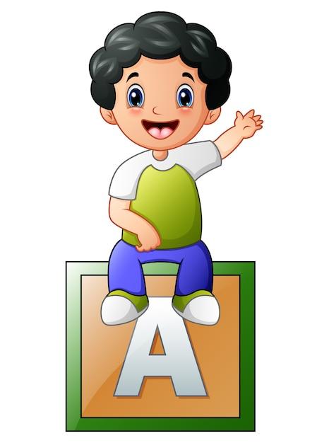 Little boy sitting on alphabet cube Premium Vector