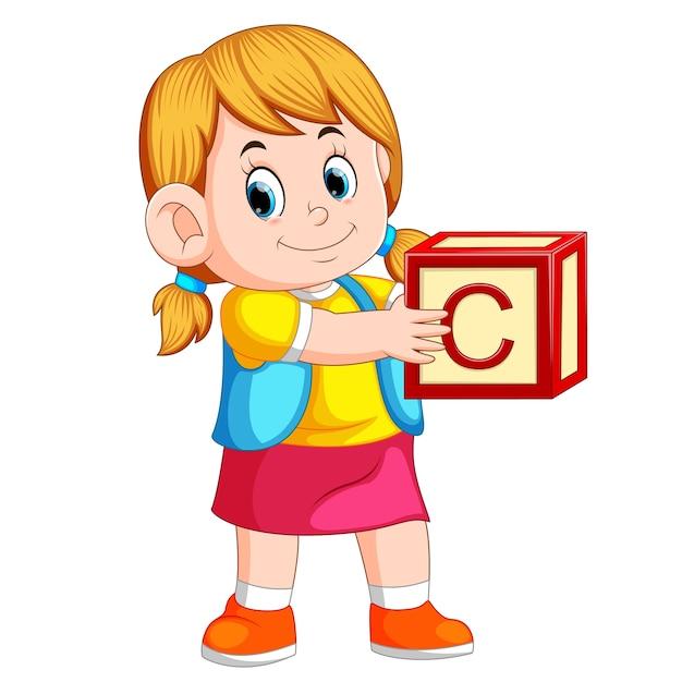 Маленькая девочка, держащая кубик алфавита Premium векторы