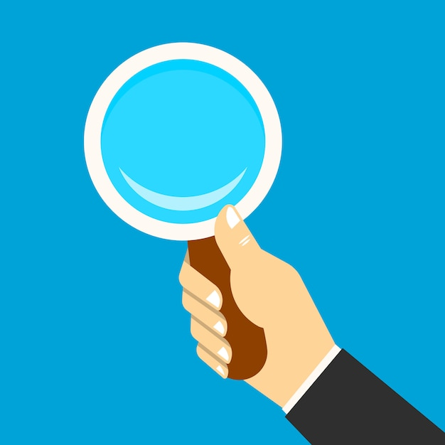 Magnifying glass in a hand Free Vector