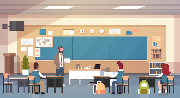 Male teacher and pupils in classroom on lesson teaching school class Premium Vector