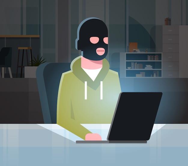 Человек черная маска сидит на компьютере Premium векторы