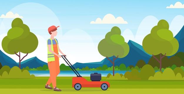Man gardener in uniform cutting grass with lawn mower gardening concept beautiful river mountains landscape background flat full length horizontal Premium Vector