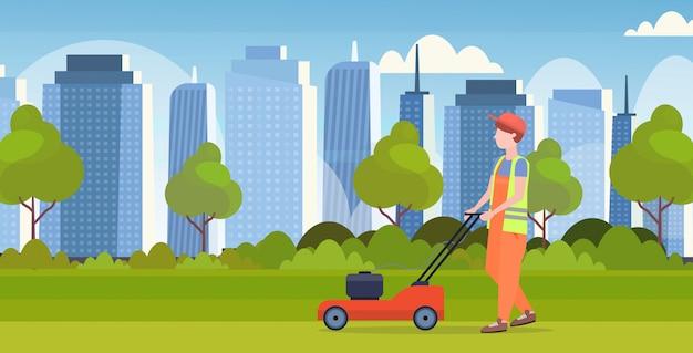Man gardener in uniform cutting grass with lawn mower gardening concept modern cityscape background flat full length horizontal Premium Vector