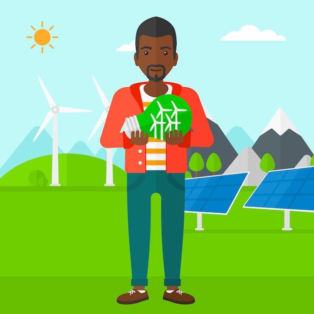 Man holding lightbulb with windmills inside Premium Vector