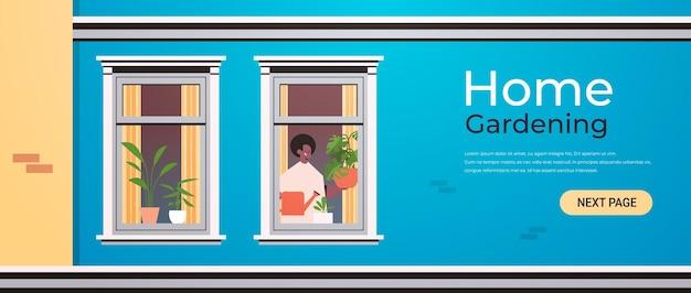 Мужчина держит лейку и наливает растения концепция домашнего садоводства афро-американский парень заботится о комнатных растениях в окне дома портрет горизонтальной копии пространства иллюстрации Premium векторы