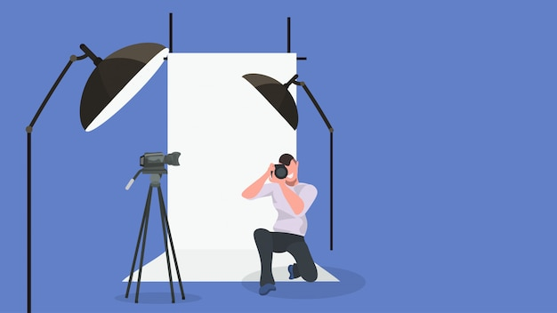 Man photographer taking photo with camera male character standing on knee and shooting modern photo studio interior with lightning equipment horizontal full length Premium Vector