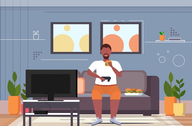 Человек сидя на диване ест гамбургер с помощью джойстика игровой коврик избыточный вес парень курсирует видеоигры на тв концепция нездоровый образ жизни интерьер гостиной горизонтальный полная длина Premium векторы