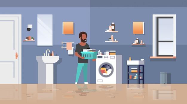 Человек с корзиной для одежды стоит возле стиральной машины Premium векторы