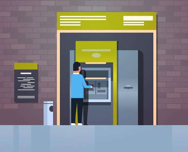 Man withdrawing cash via atm Premium Vector