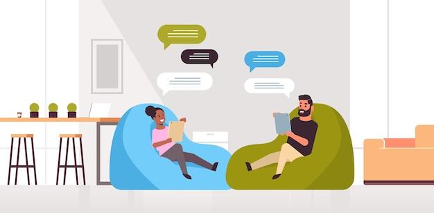 男性女性チャットメッセージングミックスレースカップルタブレットソーシャルネットワークチャットバブル通信でモバイルアプリを使用して豆袋に座っています。 Premiumベクター