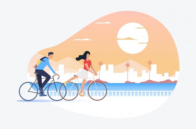 Uomo e donna in sella a biciclette, sole e paesaggio urbano in background Vettore gratuito