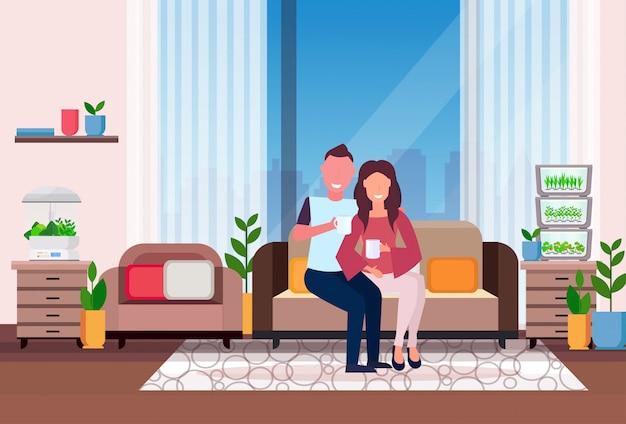 ソファに座っている男性女性カップルコーヒーを飲む現代アパートリビングルームインテリアホーム電子テラリウムガラスコンテナー家植物成長コンセプトフラット水平 Premiumベクター