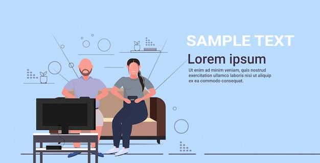 ジョイスティックのゲームパッドを使用してソファに座っている男性女性太りすぎのカップルテレビ肥満でビデオゲームを重ねる不健康なライフスタイルコンセプトフラット水平全長 Premiumベクター