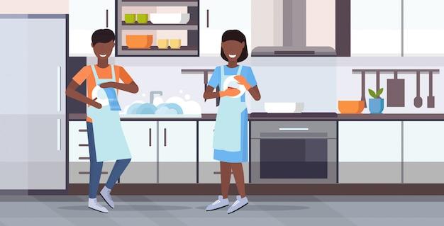 Мужчина женщина мытье посуды вытирая тарелки с полотенцем концепция мытья посуды афроамериканец пара в фартук вместе по хозяйству современная кухня интерьер горизонтальный плоский полная длина Premium векторы