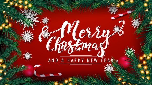 メリークリスマスと新年あけましておめでとうございます、花輪と赤いポストカード、クリスマスツリーの枝のフレーム、赤いボール、キャンディー缶と紙の雪片、上面図 Premiumベクター