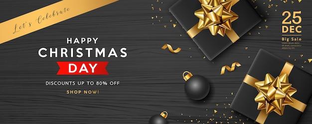 메리 크리스마스 판매, 검은 선물 상자 황금 리본 프리미엄 벡터