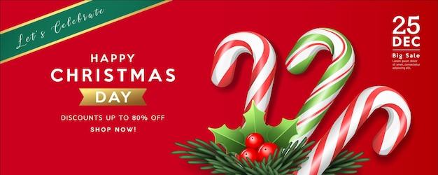 메리 크리스마스 판매 다채로운 사탕 지팡이 홀리, 빨간색 배경 인사말 카드에 소나무 잎 프리미엄 벡터