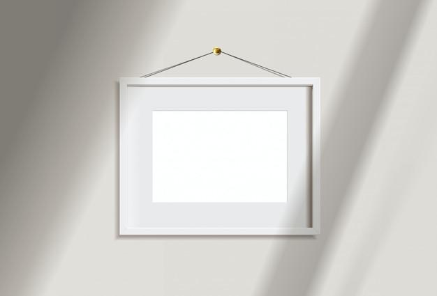 Изображение рамки минимального пустого ландшафта белое вися на белой стене с светом и тенью окна. изолировать иллюстрации. Premium векторы
