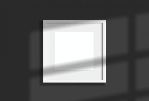 Изображение минимальной пустой квадратной белой рамки вися на темной стене с светом и тенью окна. изолировать иллюстрации. Premium векторы