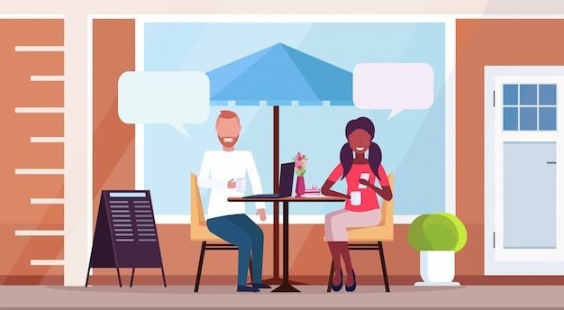 Mix race couple sitting cafe table chat bubble communication concept street restaurant terrace outdoor cafeteria exterior flat horizontal full length Premium Vector
