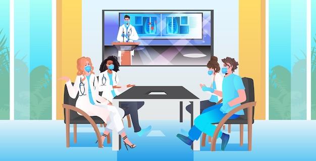 ビデオ通話中に話し合うマスクの仮想会議医療専門家を持つ混血医師チーム Premiumベクター