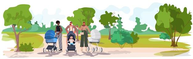 Mix race mothers walking with newborn babies in strollers motherhood concept urban park landscape background Premium Vector