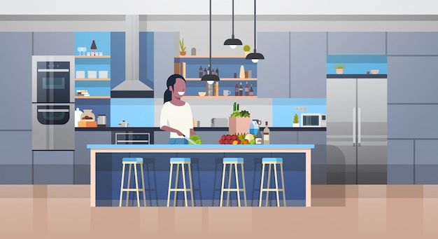 Modern kithcen interior and young african american woman cooking salad Premium Vector