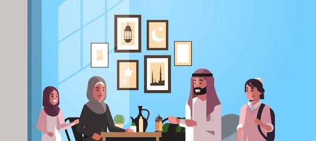 Мусульманская семья празднует рамадан карим святой месяц интерьер гостиной арабские родители и дети в традиционной одежде проводят время вместе плоский горизонтальный портрет Premium векторы