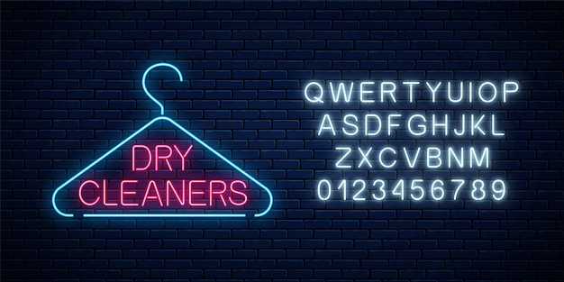 Neon dry cleaners glowing sign with hanger on a dark brick wall Premium Vector