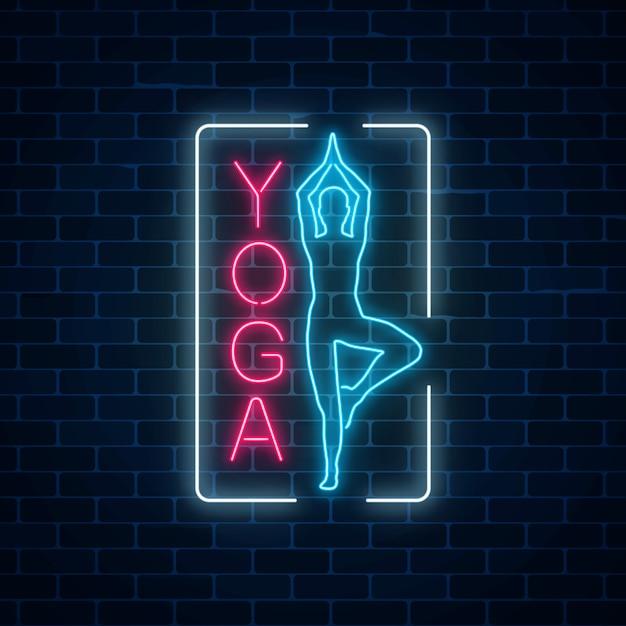 Неоновый светящийся знак упражнения йоги в прямоугольник кадра на темном фоне кирпичной стены. Premium векторы