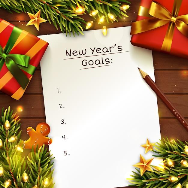 Новогоднее понятие целей с бумажным листом. деревянный стол украшен подарочной коробкой, ветками елки и гирляндами. Premium векторы