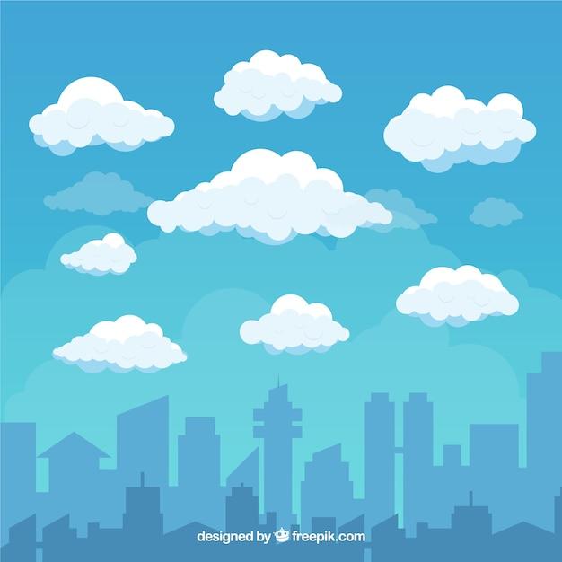 フラットスタイルの雲と都市の背景の空 無料ベクター