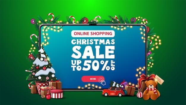 オンラインショッピング、クリスマスセール、画面上のオファーとボタン付きの大きなタブレットとギフト付きのポットのクリスマスツリーの割引バナー Premiumベクター