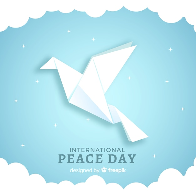 Origami dove with stars and clouds around it Free Vector