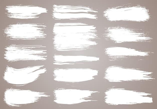Paint brush. white ink grunge brush strokes. grunge design elements. painted ink stripes. Premium Vector