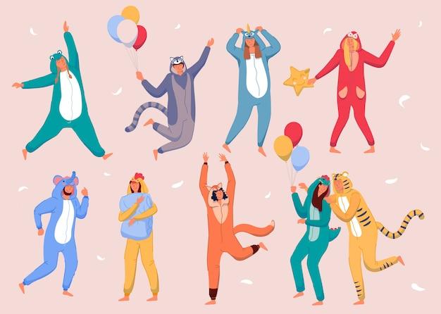 Домашняя вечеринка в пижаме. счастливые люди в костюмах животных и празднуют праздник. молодые мужчины и женщины, герои мультфильмов в кигуруми, развлекаются дома с воздушными шарами для пижамной вечеринки и летающими перьями Premium векторы
