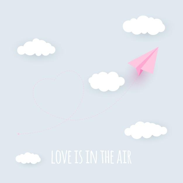 紙飛行機の心臓の背景。愛は空中の概念です。 Premiumベクター