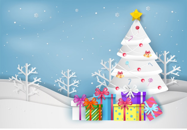 Paper art style of christmas tree and colorful gift box in winter with landscape backgroun Premium Vector