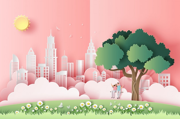Paper art style of cute couple sitting on a swing under a tree in a big city. Premium Vector