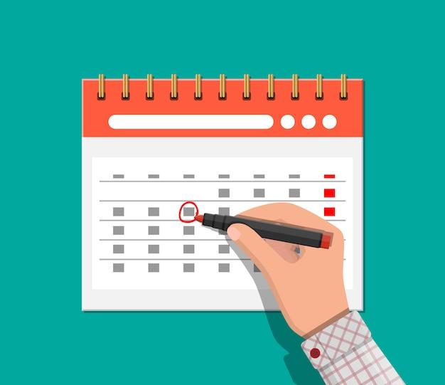Paper spiral wall calendar. hand with pen Premium Vector