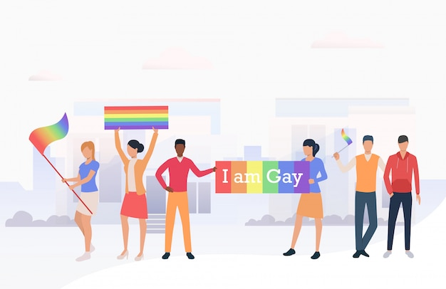 People holding lgbtq flags and i am gay banner in parade Free Vector