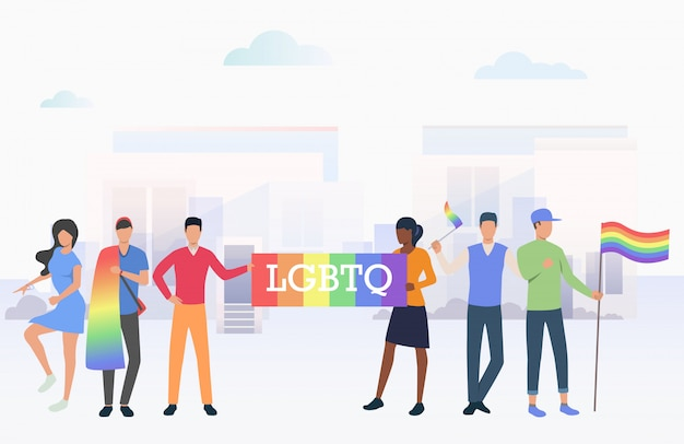 People holding lgbtq flags in pride parade in city Free Vector