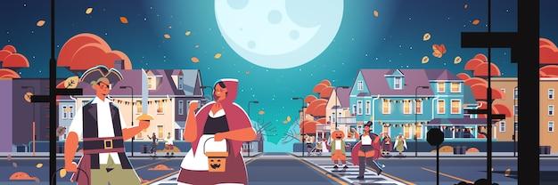 마을 트릭을 걷는 의상 사람들 또는 해피 할로윈 축하 개념 인사말 카드 수평 벡터 일러스트 레이 션을 치료 프리미엄 벡터