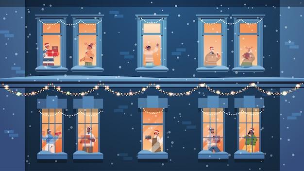 선물을 들고 산타 모자에있는 사람들은 창틀에 서있는 인종 이웃을 혼합합니다 새해 크리스마스 휴일 축하 자기 격리 개념 건물 집 외관 수평 벡터 일러스트 레이션 프리미엄 벡터