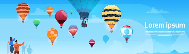 People looking at colorful air balloons flying in sky banner Premium Vector
