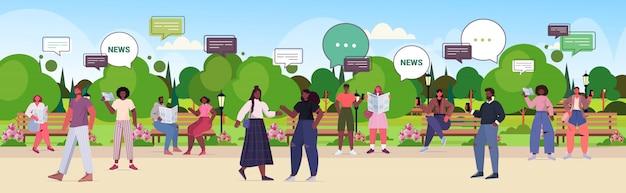 新聞を読んで、毎日のニュースチャットバブル通信の概念を議論する人々。都市公園の完全な長さの水平方向の図を歩いて混血男性女性 Premiumベクター