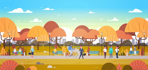 People relaxing outdoors in autumn urban park over city skyline walking riding bicycle and communicating Premium Vector