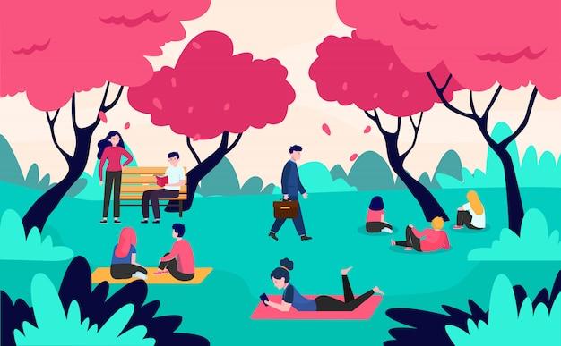 Persone che si rilassano nel parco con alberi di ciliegio in fiore rosa Vettore gratuito