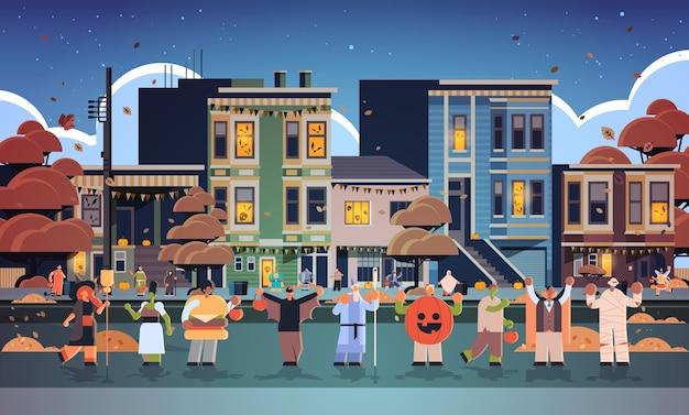 Люди в костюмах разных монстров гуляют по городу трюки и угощают счастливой вечеринкой в честь хэллоуина концепция празднования улица города здания внешний вид городской пейзаж Premium векторы